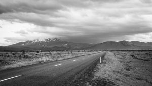 road leading to mountains with dramatic clouds overhead