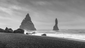 sea stacks pummeled by the surf on a black sand beach