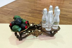 scale with grenades on one end and water bottles on the other