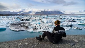 woman viewing a glacial lagoon in iceland