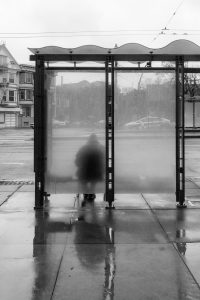 person waiting at a bus stop in the rain