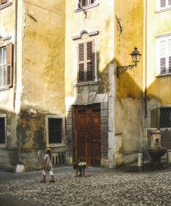 children playing in the streets of a historic neighborhood in Italy