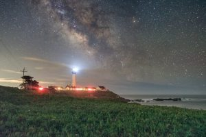 the milky way above a lighthouse on the pacific coast