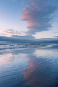 cloud catching sunset light reflected on a beach