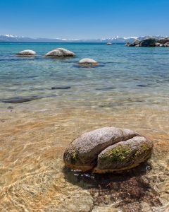 smooth round boulders in clear alpine lake water