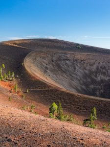 sweeping curves of a volcanic landscape dotted by trees with two tiny figures at the top