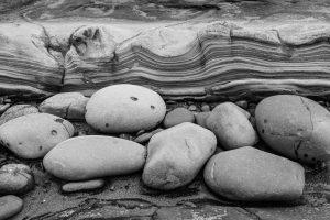 smooth rocks lying on sand near a layered stone shelf