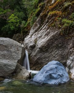 a small waterfall spilling out between large rocks