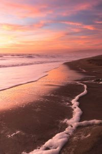 a line of sea foam left behind on the beach by the receding surf at sunset