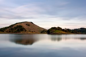 rolling california hills reflected in a calm lake