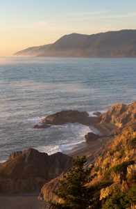 rocky pacific coast at sunset with distant mountains