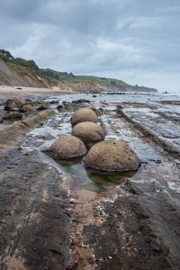 smooth round rocks arranged in a line on the beach